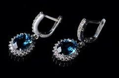 Ασημένια σκουλαρίκια με το μπλε topaz σε ένα μαύρο υπόβαθρο Στοκ Φωτογραφία