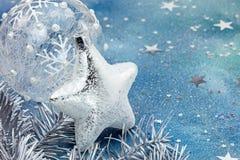 Ασημένια σφαίρα Χριστουγέννων αστεριών και γυαλιού στο μπλε υπόβαθρο Στοκ Φωτογραφία