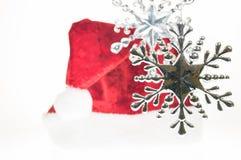 Ασημένιες κρεμώντας snowflake Χριστουγέννων διακοσμήσεις με το καπέλο Santa Στοκ φωτογραφία με δικαίωμα ελεύθερης χρήσης