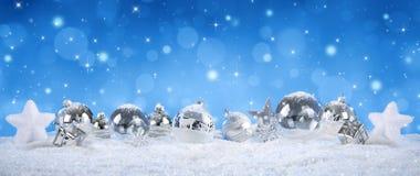 Ασημένιες σφαίρες στο χιόνι με τις χιονοπτώσεις Στοκ Εικόνες