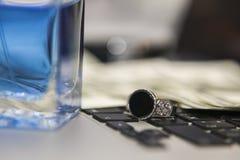 Ασημένιοι δαχτυλίδι, άρωμα, δολάρια και υπολογιστής Στοκ Φωτογραφίες