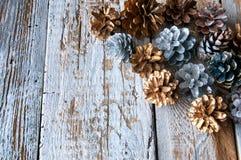 Ασημένιοι και χρυσοί κώνοι στο άσπρο ξύλινο backgound Copyspace Στοκ Φωτογραφία
