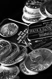 Ασημένιοι νομίσματα και φραγμοί που αντιπροσωπεύουν τον πλούτο στοκ εικόνες