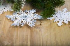 Ασημένιοι snowflakes και κλάδοι έλατου σε έναν ξύλινο πίνακα Χριστούγεννα Στοκ φωτογραφίες με δικαίωμα ελεύθερης χρήσης
