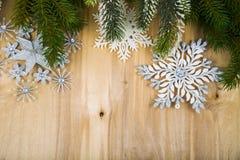Ασημένιοι snowflakes και κλάδοι έλατου σε έναν ξύλινο πίνακα Χριστούγεννα Στοκ Εικόνες