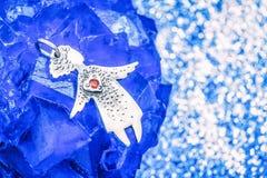 Ασημένιος άγγελος κρεμαστών κοσμημάτων με μια κόκκινη καρδιά σε μια μπλε πέτρα στοκ εικόνες
