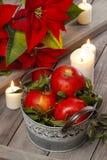 Ασημένιος κάδος των κόκκινων ώριμων μήλων μεταξύ των κεριών Στοκ Φωτογραφίες