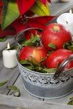 Ασημένιος κάδος των κόκκινων ώριμων μήλων μεταξύ των κεριών Στοκ Εικόνες