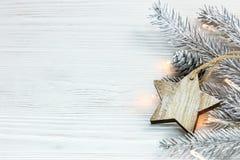 Ασημένιος κλάδος χριστουγεννιάτικων δέντρων με την καμμένος γιρλάντα και ξύλινο sta Στοκ εικόνα με δικαίωμα ελεύθερης χρήσης