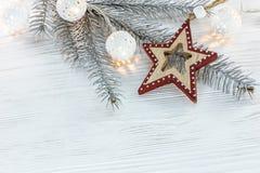 Ασημένιος κλάδος χριστουγεννιάτικων δέντρων με την καμμένος ελαφριά γιρλάντα και το χέρι Στοκ εικόνες με δικαίωμα ελεύθερης χρήσης