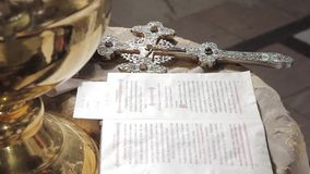 Ασημένιος ορθόδοξος σταυρός στο βωμό δίπλα στη Βίβλο στην εκκλησία Βρίσκεται στην επιτραπέζια κινηματογράφηση σε πρώτο πλάνο απόθεμα βίντεο