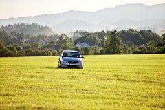 Ασημένιο αυτοκίνητο σε ένα πράσινο πεδίο στοκ φωτογραφία με δικαίωμα ελεύθερης χρήσης