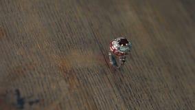 Ασημένιο δαχτυλίδι με το σμάλτο και πολύτιμοι λίθοι σε μια ξύλινη επιφάνεια απόθεμα βίντεο