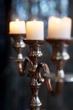 Ασημένιο κηροπήγιο με τρία καίγοντας άσπρα κεριά στο σκοτεινό υπόβαθρο Στοκ Φωτογραφία
