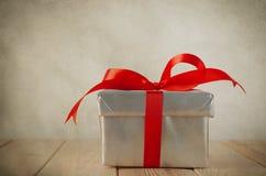 Ασημένιο κιβώτιο δώρων με το κόκκινο τόξο - τρύγος Στοκ Εικόνα