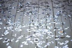 Ασημένιο κομφετί που διασκορπίζεται σε ένα άσπρο ξύλινο πάτωμα Νέο συμβαλλόμενο μέρος έτους στοκ φωτογραφία