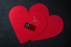 Ασημένιο κρεμαστό κόσμημα καρδιών σε δύο κόκκινα πιλήματα καρδιών Στοκ φωτογραφία με δικαίωμα ελεύθερης χρήσης