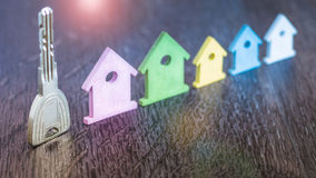Ασημένιο κλειδί που μένει σύμφωνα με το μικροσκοπικό σύμβολο των διάφορων χρωματισμένων σπιτιών στη σκοτεινή ξύλινη επιφάνεια στοκ εικόνες με δικαίωμα ελεύθερης χρήσης