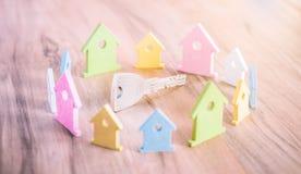 Ασημένιο κλειδί στην ξύλινη επιφάνεια που περιβάλλεται με την παραμονή μικροσκοπικό σύμβολο των σπιτιών στα διαφορετικά χρώματα στοκ φωτογραφία