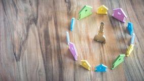 Ασημένιο κλειδί στην ξύλινη επιφάνεια που περιβάλλεται με την παραμονή μικροσκοπικό σύμβολο των σπιτιών στα διαφορετικά χρώματα στοκ εικόνα