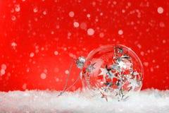Ασημένιο μονοχρωματικό μπιχλιμπίδι Χριστουγέννων στο κόκκινο στοκ εικόνα