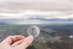 Ασημένιο νόμισμα Bitcoin, λαβή χεριών bitcoin επάνω από την πόλη στοκ εικόνα