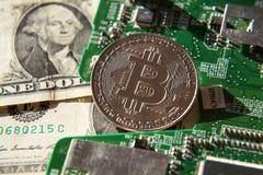 Ασημένιο νόμισμα bitcoin με τα δολάρια και τη μητρική κάρτα υπολογιστών, έννοια μεταλλείας cryptocurrency Στοκ Εικόνες