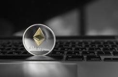 Ασημένιο νόμισμα Ethereum με το χρυσό σύμβολο Ethereum σε ένα πληκτρολόγιο lap-top Ανταλλαγή, επιχείρηση, εμπορική Κέρδος από τη  στοκ εικόνα