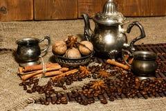 Ασημένιο δοχείο καφέ στο υπόβαθρο των φασολιών και των καρυδιών καφέ Στοκ φωτογραφίες με δικαίωμα ελεύθερης χρήσης