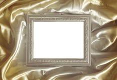 Ασημένιο πλαίσιο στο χρυσό μετάξι υφάσματος Στοκ Φωτογραφία