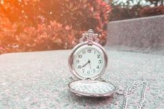 Ασημένιο ρολόι τσεπών σε μια καρέκλα πετρών Στοκ Φωτογραφία