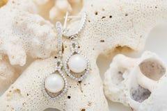 Ασημένιο σκουλαρίκι με το μαργαριτάρι και διαμάντια στο κοράλλι στοκ εικόνα