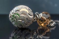 Ασημένιο σκουλαρίκι με τους ηλέκτρινους πολύτιμους λίθους στο σκοτεινό υπόβαθρο με beautyful στοκ εικόνες
