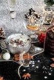 Ασημένιο φλυτζάνι καρτών Χριστουγέννων της γλυκιάς κρέμας και ποτήρι της σαμπάνιας στο μαύρο πίνακα, με τα γλυκά, κανέλα, γλυκάνι στοκ φωτογραφία
