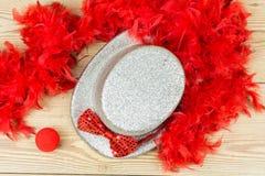 Ασημένιο ψηλό καπέλο, κόκκινο χνουδωτό boa φτερών, κόκκινος δεσμός τόξων και κόκκινο clo Στοκ Εικόνες