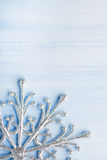 Ασημένιο snowflake Χριστουγέννων στο ανοικτό μπλε ξύλινο υπόβαθρο με το διάστημα για το κείμενο Στοκ Φωτογραφία
