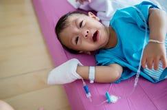 Ασθένεια παιδιών Λίγο μωρό που συνδέει τον ενδοφλέβιο σωλήνα με του ασθενή παραδίδει το νοσοκομειακό κρεβάτι Άρρωστοι μωρών και ν στοκ φωτογραφία με δικαίωμα ελεύθερης χρήσης