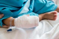 Ασθένεια παιδιών Λίγο μωρό που συνδέει τον ενδοφλέβιο σωλήνα με του ασθενή παραδίδει το νοσοκομειακό κρεβάτι στοκ εικόνες με δικαίωμα ελεύθερης χρήσης