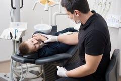 Ασθενής αγοριών με τον πονόδοντο που παραπονιέται στον παιδιατρικό οδοντίατρο στο οδοντικό γραφείο κλινικών Στοκ φωτογραφία με δικαίωμα ελεύθερης χρήσης