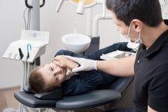 Ασθενής αγοριών με τον πονόδοντο που παραπονιέται στον παιδιατρικό οδοντίατρο στο οδοντικό γραφείο κλινικών Στοκ εικόνα με δικαίωμα ελεύθερης χρήσης