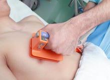 Ασθενής γιατρών reanimates από ηλεκτρικός defibrillator Στοκ Εικόνες