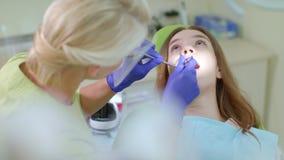 Ασθενής με τη συνεδρίαση πονόδοντου στην καρέκλα οδοντιάτρων  φιλμ μικρού μήκους