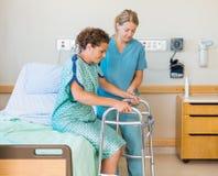 Ασθενής με τον περιπατητή ενώ νοσοκόμα που βοηθά την μέσα Στοκ Εικόνες