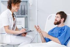 Ασθενής νοσοκομείου που μιλά με τη νοσοκόμα Στοκ Εικόνες