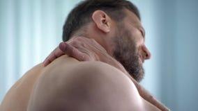 Ασθενής νοσοκομείου που τρίβει το λαιμό, που αισθάνεται το νωτιαίο πόνο, επίπονος σπασμός, ιατρική στοκ εικόνες με δικαίωμα ελεύθερης χρήσης