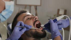 Ασθενής που έχει την οδοντική θεραπεία στο γραφείο οδοντιάτρων ` s Άτομο που επισκέπτεται τον οδοντίατρό της απόθεμα βίντεο