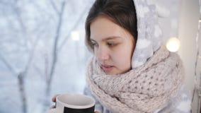 Ασθενής χειμώνας εφήβων κοριτσιών στις πυτζάμες μου, καθμένος στο παράθυρο και το καυτό τσάι Viet απόθεμα βίντεο