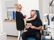 Ασθενής optometrist στο γραφείο για την εξέταση ματιών στοκ φωτογραφία
