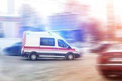 Ασθενοφόρο που συναγωνίζεται μέσω της κυκλοφοριακής συμφόρησης πόλεων στον ολισθηρό δρόμο με slush το χιόνι Τροχαίο στην εθνική ο στοκ εικόνα με δικαίωμα ελεύθερης χρήσης