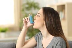 Ασθματική γυναίκα που χρησιμοποιεί inhaler στοκ φωτογραφία